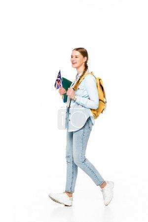 Lächelndes Mädchen mit Zopf und Rucksack, das mit der Fahne des vereinigten Königreichs und auf weißem Papier isolierten Werbeschriften spazieren geht