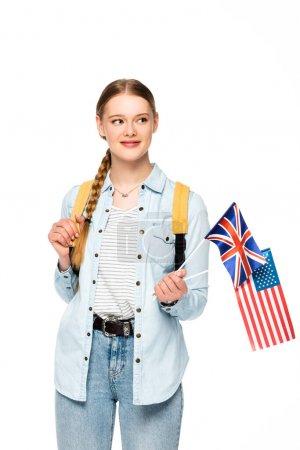Photo pour Petite fille souriante avec tresse et sac à dos tenant drapeaux d'amérique et royaume uni isolée sur blanc - image libre de droit