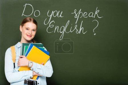 Photo pour Fille souriante avec copybooks et sac à dos debout près du tableau avec parlez-vous lettrage anglais - image libre de droit