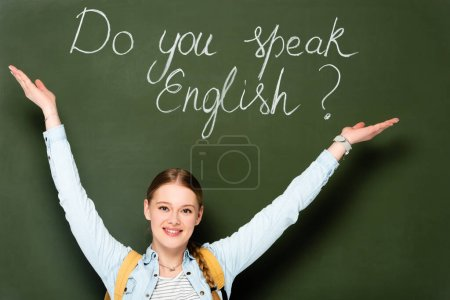 smiling girl with backpack pointing at chalkboard with do you speak English lettering
