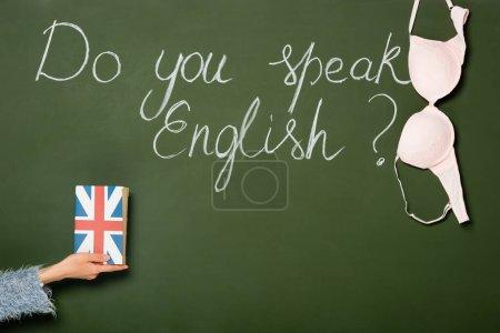 Photo pour Vue recadrée de fille tenant livre avec drapeau britannique près de tableau avec parlez-vous lettrage anglais et soutien-gorge - image libre de droit