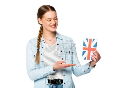 Photo for Smiling pretty girl with braid presenting book with uk flag isolated on white - Royalty Free Image