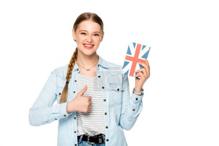 smiling pretty girl with braid holding book with uk flag and showing thumb up isolated on white