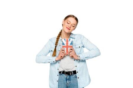 Photo pour Sourire jolie fille avec tresse et les yeux fermés tenant livre avec drapeau britannique isolé sur blanc - image libre de droit