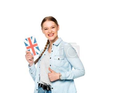 Photo pour Souriant jolie fille avec tresse tenant livre avec drapeau britannique et montrant pouce vers le haut isolé sur blanc - image libre de droit