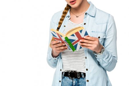 cropped view of girl with braid reading book with uk flag isolated on white