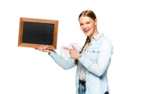 Photo for Smiling pretty girl with braid pointing at empty chalkboard isolated on white - Royalty Free Image