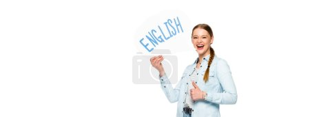 Photo for Smiling girl with braid holding speech bubble with English lettering and showing thumb up isolated on white, panoramic shot - Royalty Free Image