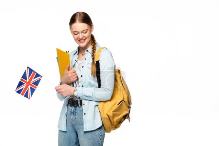 smiling girl with backpack holding copybooks and uk flag isolated on white