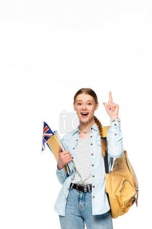 Photo pour Fille excitée avec sac à dos pointant vers le haut et tenant des copybooks et drapeau britannique isolé sur blanc - image libre de droit
