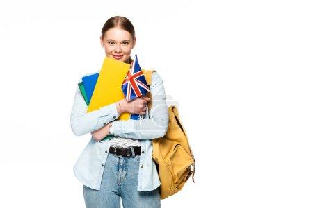 Photo pour Fille souriante avec sac à dos tenant des copybooks et drapeau britannique isolé sur blanc - image libre de droit