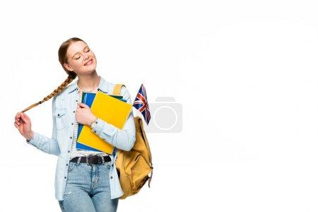 Photo pour Une fille souriante avec sac à dos tenant des cahiers et un drapeau et touchant une tresse isolée sur blanc - image libre de droit