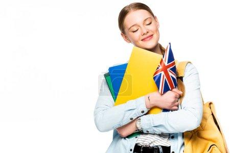 Photo pour Fille souriante avec sac à dos et les yeux fermés tenant copybooks et drapeau britannique isolé sur blanc - image libre de droit