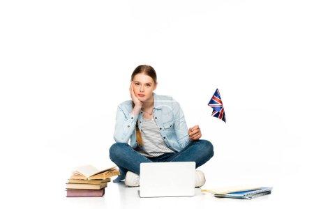 Photo pour Triste fille assise sur le sol avec un ordinateur portable, des livres et des cahiers et tenant le drapeau britannique isolée sur blanc - image libre de droit