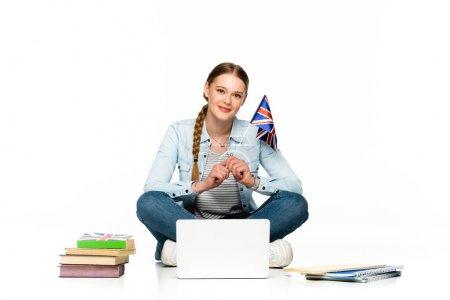 Photo pour Une jeune fille souriante assise sur le sol avec son ordinateur portable, ses livres et ses cahiers et tenant son drapeau isolé sur un blanc - image libre de droit