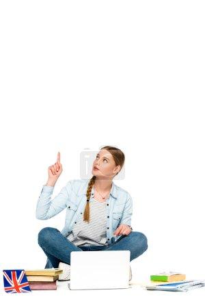 Photo pour Fille assise sur le sol avec ordinateur portable, livres et copybooks, drapeau britannique et pointant vers le haut isolé sur blanc - image libre de droit