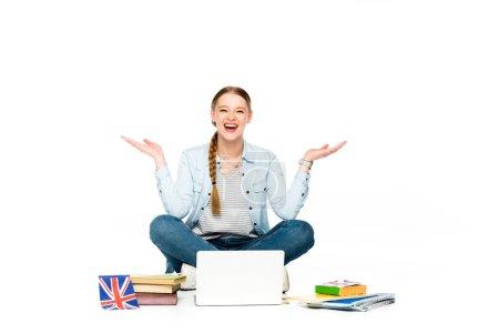Photo pour Fille heureuse assise sur le sol avec ordinateur portable, livres et copybooks, drapeau britannique et geste isolé sur blanc - image libre de droit