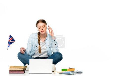 Photo pour Fille assise sur le sol dans des écouteurs près d'un ordinateur portable, livres et copybooks, tenant drapeau britannique isolé sur blanc - image libre de droit