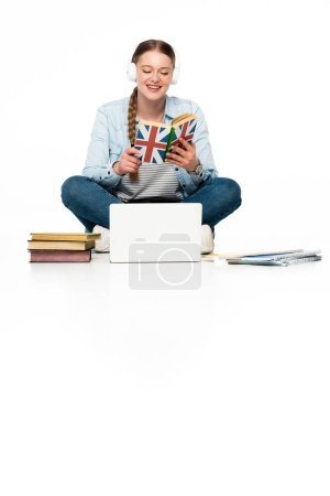 Photo pour Une jeune fille souriante qui apprend l'anglais par terre dans des écouteurs près d'un ordinateur portable, des livres et un cahier isolés sur blanc - image libre de droit