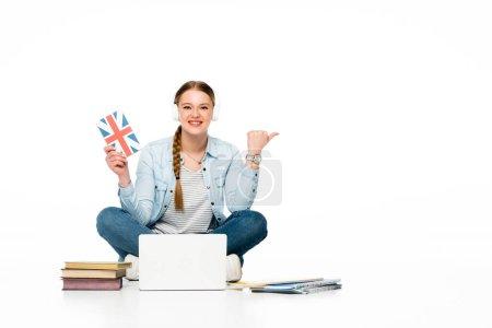 Photo pour Une fille souriante apprenant l'anglais par terre dans des écouteurs près d'un ordinateur portable, de livres et d'un cahier et pointant du doigt isolé sur blanc - image libre de droit