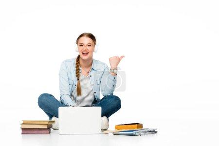Photo pour Fille souriante assise sur le sol dans des écouteurs près d'un ordinateur portable, des livres et des copybooks et pointant de côté isolé sur blanc - image libre de droit