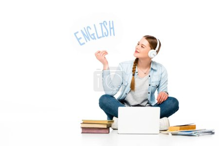 smiling girl sitting on floor in headphones with speech bubble with english lettering near laptop, books and copybooks isolated on white