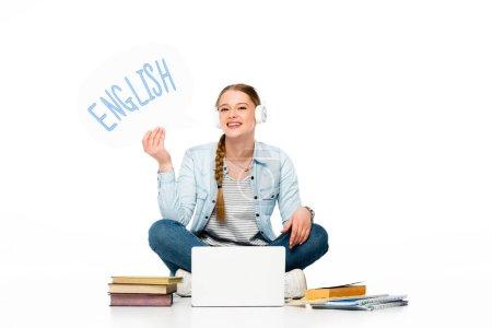Photo pour Une jeune fille souriante assise au sol dans des écouteurs avec une bulle vocale avec des lettres anglaises près d'un ordinateur portable, des livres et des cahiers isolés sur du blanc - image libre de droit