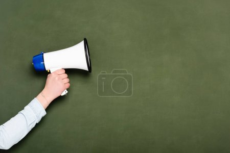 cropped view of woman holding loudspeaker on chalkboard background