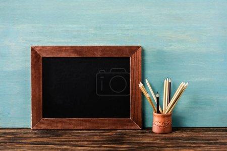 Photo pour Tableau noir vide près des crayons sur la table en bois près du mur bleu - image libre de droit