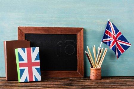 Photo pour Tableau vide près des crayons, des livres et du drapeau sur une table en bois près d'un mur bleu - image libre de droit