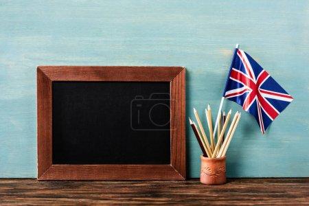 Photo pour Tableau vide près des crayons et drapeau du Royaume-Uni sur une table en bois près du mur bleu - image libre de droit