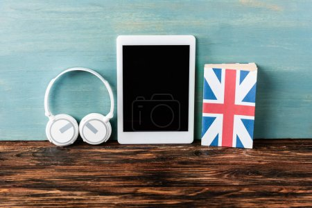 headphones, digital tablet with blank screen and uk flag on wooden table near blue wall