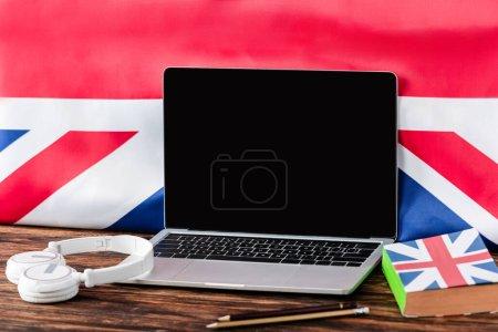 Photo pour Ordinateur portable près du livre avec drapeau britannique et écouteurs sur table en bois - image libre de droit