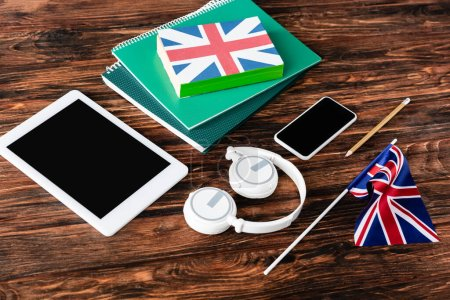 Photo for Gadgets near books and copybooks and uk flags on wooden table - Royalty Free Image