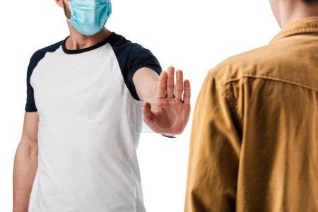 Photo pour Vue recadrée de l'homme en masque médical montrant geste d'arrêt près du gars isolé sur blanc - image libre de droit