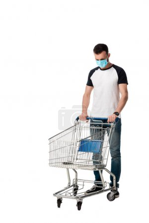 man in medical mask standing near empty shopping cart isolated on white