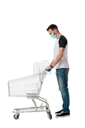 man in medical mask standing with empty shopping cart isolated on white