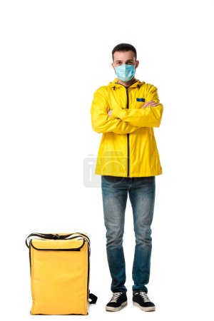 Photo for Delivery man in medical mask standing with crossed arms near bag with order isolated on white - Royalty Free Image