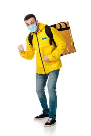 Photo for Delivery man in medical mask and backpack with order showing fists on white - Royalty Free Image