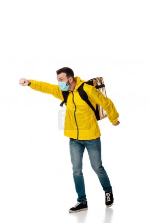 Photo for Delivery man in medical mask and backpack with order gesturing on white - Royalty Free Image