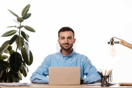 Photo pour Freelance heureux en utilisant un ordinateur portable près de l'usine isolé sur l'espace de travail blanc - image libre de droit