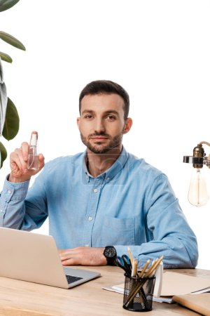Photo for Freelancer holding hand sanitizer near laptop isolated on white - Royalty Free Image