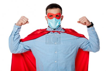 Photo for Man in superhero costume and medical mask showing muscles isolated on white - Royalty Free Image