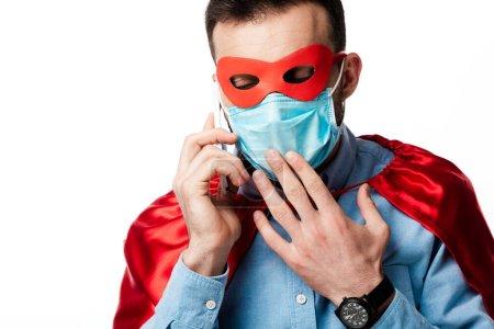 Photo pour Homme en costume de super-héros et masque médical parlant sur smartphone isolé sur blanc - image libre de droit