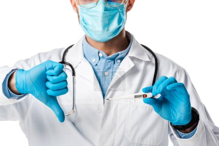Photo for Cropped view of doctor in medical mask and white coat holding digital thermometer and showing thumb down isolated on white - Royalty Free Image