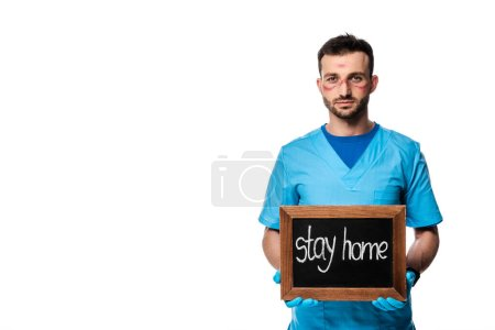 Photo for Doctor with marks on face holding chalk board with stay home lettering isolated on white - Royalty Free Image