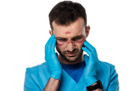 tired doctor with marks on face touching head isolated on white