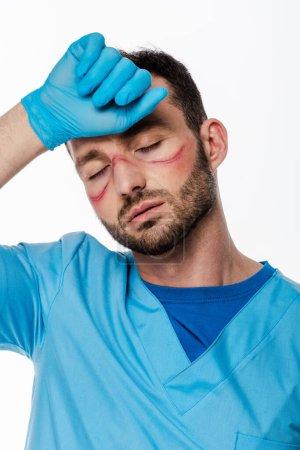 Photo pour Médecin fatigué avec des marques sur le visage et les yeux fermés touchant le front isolé sur blanc - image libre de droit
