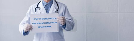 Photo for Panoramic shot of middle aged doctor in latex gloves holding placard with i stay at work for you, you stay at home for us lettering on grey - Royalty Free Image