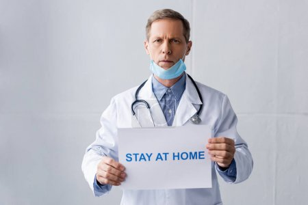 Photo pour Médecin mature en masque médical tenant une pancarte avec inscription de séjour à la maison sur gris - image libre de droit